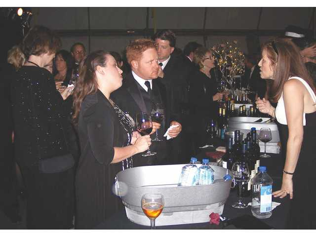 Michelle and Jason Crawford learn about the wine they are drinking from one of the vendors pouring at the reception for the Golden Goose Gala.