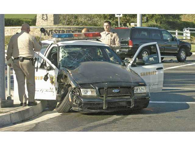 CHP officers investigate a crash that occured at the intersection of The Old Road and Valencia Blvd. on Thursday. The driver of a Cadillac Escalade, background, collided with a sheriff's patrol car that was responding to a call.