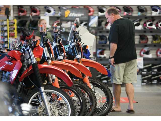 Tim Mendenhall, of Saugus, look over some motorcycles at the SCV MotorSport store in Newhall, Wednesday afternoon.
