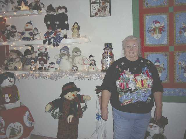 "Gayle Mitchell and a few of her many snowmen she has collected. Mitchell, of Newhall, captured the ""Best Theme"" prize from the 15th annual Holiday Light Tour. She welcomes all to visit her Newhall home."
