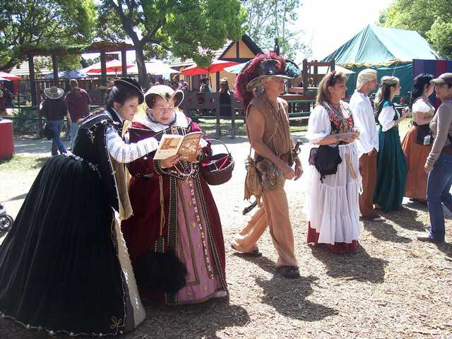 Two ladies of the court examine the Faire program.