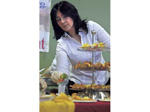 Roza Hamzehei, owner of Bella Cucina Ristorante Italiano, refils a display platter at the Taste of Expo at the Santa Clarita Sports Complex on Friday.