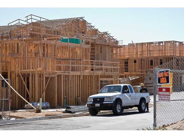 A worker at construction site off of Tesoro Del Valle in Saugus gets tools out of a truck on Monday afternoon.