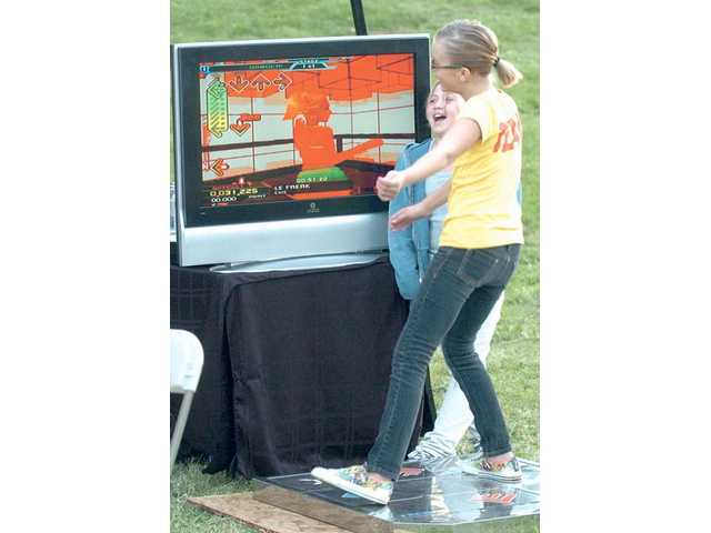Jillian Brimigion, 10, right, matches steps to a song on a Dance-Dance Revolution machine at the Castaic Days event held at Castaic Lake on Oct.9.  Her friend Mollie Pettit, also 10, watches while waiting for her turn.