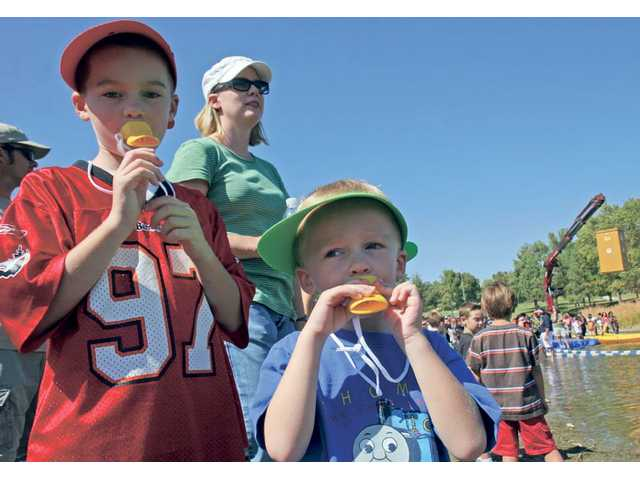 Dylan Brunson , 7, and brother Tyler, 4,cheer on three ducks their mother, Kim, behind, purchased at the 7th Annual Rubber Ducky Regatta at Castaic Lake on Saturday. Proceeds go to Samuel Dixon Family Health Centers.