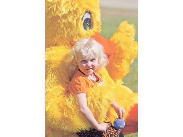 Three-year-old Megan Saxton of Stevenson Ranch poses for photos with a duck character at the 7th Annual Rubber Ducky Regatta.