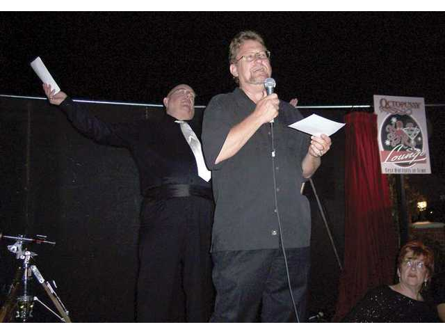"TimBen Boydston, front, and Greg Finley work to fire up the crowd for the live auction at ""Casino Royale 008."""