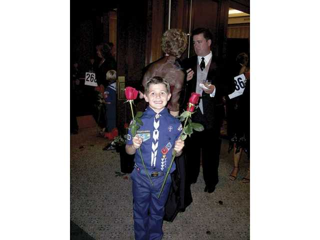 Peyton Halaby was one of several scouts presenting long-stemmed roses to women arriving at the annual Leaders of Character recognition dinner.