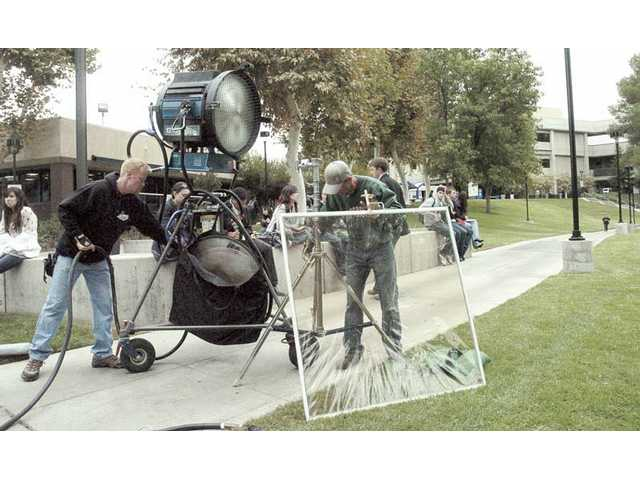 "A crew sets up to shoot a scene for the television show ""CSI"" on the COC campus as students watch Monday."