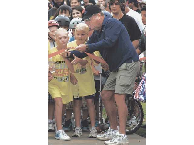 Santa Clarita City Council member Bob Keller cuts the ribbon at the start of the one mile walk for diabetes on Sunday morning at Bridgeport Park in Valencia.