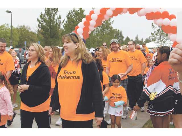Members of Team Makenna walk through the starting line during a walk to raise money in the fight against diabetes Sunday morning at Bridgeport Park.