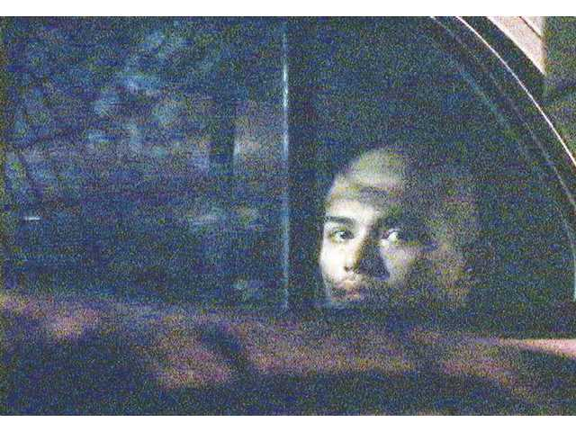 A suspect in Saturday's arrest of two gang members sits in a Los Angeles Sheriff's Department car awaiting transportation to county jail for booking.