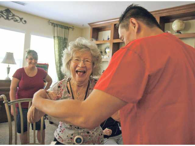 Resident Fay Dicker dances with head caregiver Jay Valenzuela at Mameleh Patleh's Upscale Senior House in Canyon Country as caregiver Rachael Chavira watches