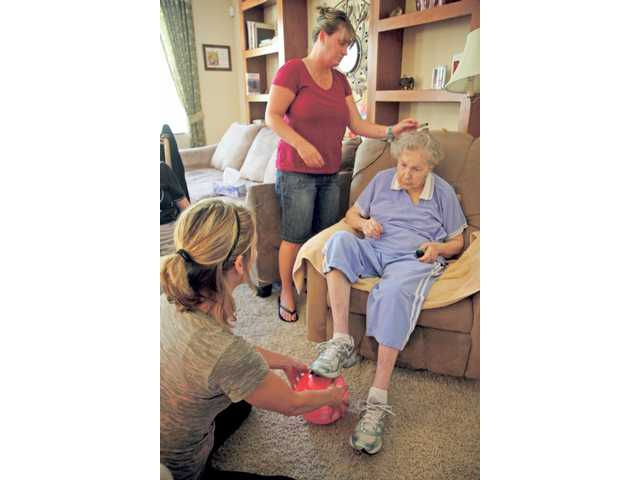 Resident Joyce Whiteside, seated, receives care from Chavira, center, and Kimberly Nunley.