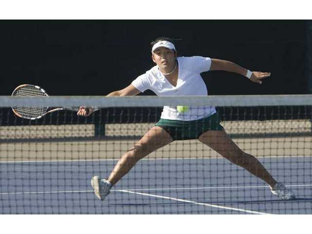 Canyon High School singles player Chika Kondo stretches herself in order to reach the ball hit by Valencia High opponent Isabella Fraczek on Saturday morning during the annual Valencia Fall Brawl tournament.