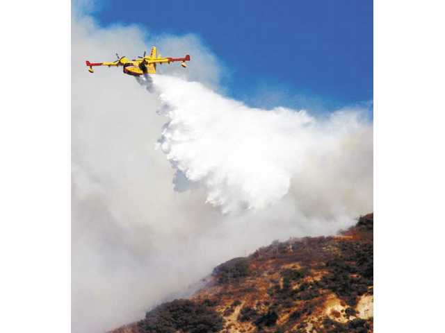 An aircraft drops a load of water on a wildfire, in the Angeles National Forest on Sunday. The blaze threatened homes in the vicinity of Kagel and Lopez canyons.