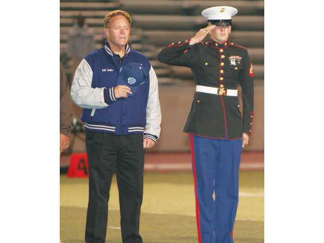 Saugus Principal Bill Bolde (left) and U.S. Marine Cpl. Bryan Warloe stand at attention as the Saugus High School band plays the National Anthem.