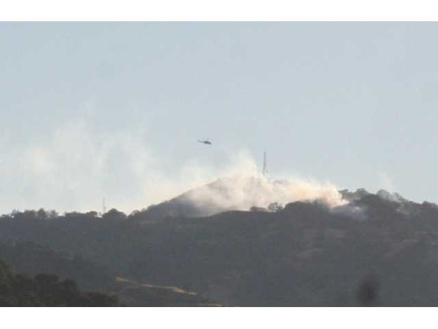 An L.A. County Fire helicopter approaches a hot spot atop the Santa Susana Mountains, seen from the Santa Clarita Valley side. The photo was taken at 6.m. Tuesday in Newhall, near the corner of Sierra Highway and Dockweiler, looking south.
