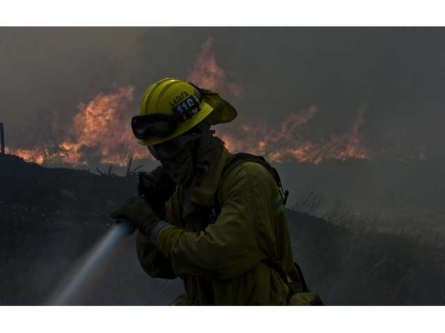 Firefighter from L.A. County Crew 116 fights a brush fire near homes off Hubbard. Fire crews from around Southern California battle the Marek fire near the 210 freeway between McClay Road and Van Nuys Blvd. in the northern San Fernando Valley. These pictures were taken from 6 a.m. to 10 a.m. Monday, Oct. 13, 2008. Residents in north Sylmar and Lake View Terrace were evacuated, and dozens of homes and vehicles were destroyed.