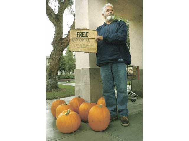 Dave Scholes of Newhall stands at a bus stop near Town Center Drive holding a sign advertising his free pumpkins with a donation Tuesday afternoon.