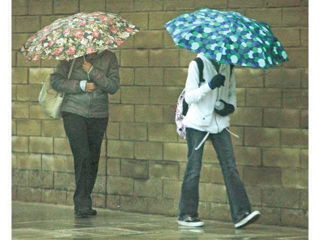 Two women sheild themselves with umbrellas as they walk in the wind and rain on the corner of Lyons Avenue and Wiley Canyon road Tuesday.