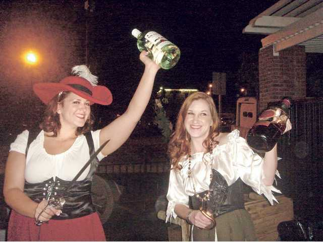 Saucy wench, Casey Rock ,left, with sister Sarah Rock, serve jugs of rum to Canyon Theatre Guild supporters during a fundraiser which sported a pirate theme.