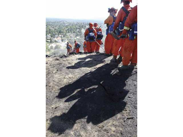 Inmate firefighting crews line up and get ready to hike down the mountain to work on hot spots left from a charred hillside off Jolette Avenue, north of Sesnon Boulevard, in Granada Hills Tuesday afternoon.