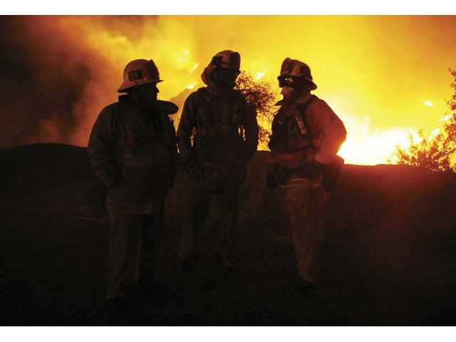 Firefighters from Los Angeles Fire Department station 24 plan attack methods against the fire as the Sesnon Fire burns behind them near Porter Ridge Park Monday night.