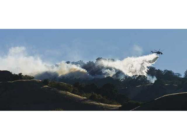 An Erickson Sky Crane drops a load of water near the crest of the Santa Susana Mountains leading into the Newhall Pass late Tuesday afternoon. Fire officials said their strategy is to let the fire simply burn itself out.