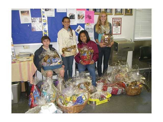 La Mesa Junior High honor students Dane Cannon, Andi Hill, Jordan Dulay and Kristie Moody sit in the lobby of the Castaic Animal Shelter with gift baskets they donated for people who adopt a pet.