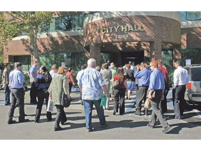 Santa Clarita City Hall employees filter back into the building after a fire alarm was triggered at the same time of the Great California ShakeOut earthquake readiness drill on the morning of Oct. 10.