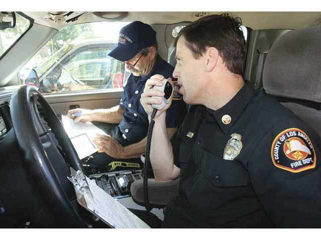 Fire Capt. Jeff Horweldel, left, and Battalion Chief Jim Robinson exchange words via radio with Santa Clarita sheriff's deputies. Firefighters practiced scanning the valley for injured victims and major safety hazards.