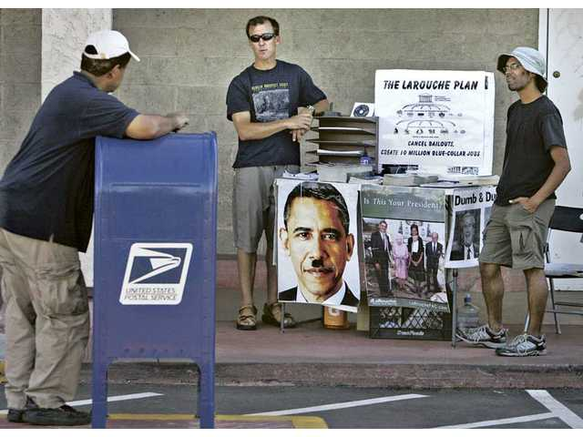 LaRouche Political Action Commitee volunteers, Eric Thomas, left, and Charles Gracia talk to a man as he drops a letter in a mail box in front of the U.S. Post Office on Lyons Avenue on Friday. The two handed out literature informing passers-by of the organization's stance.