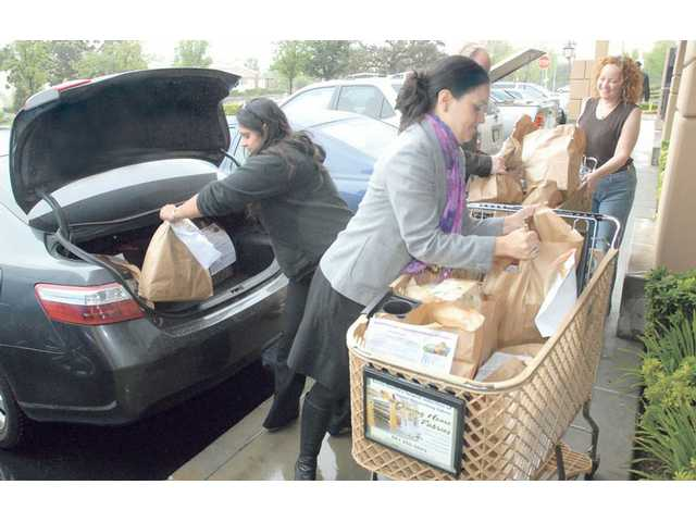 Prudence Stein lifts a bag of food from a shopping cart as Realtors of Dilbeck GMAC Real Estate load cars and trucks with an estimated five tons of food collected for the Santa Clarita Valley Food Pantry in Valencia on Oct. 17.