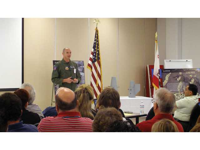 Air Force Capt. Dennis Chet Cummings addresses HR Textron employees at the company facility in Valencia on Wednesday.