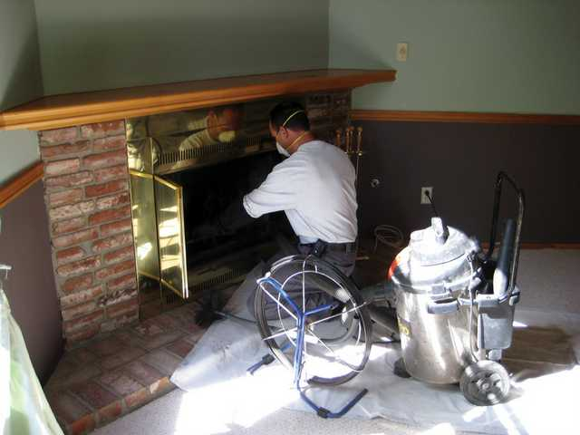 Richard Balliger Jr. vacuums a fireplace after cleaning it. With all the ash in the air from recent wildfires, cleaning your fireplace is a good idea for safety and better heating.