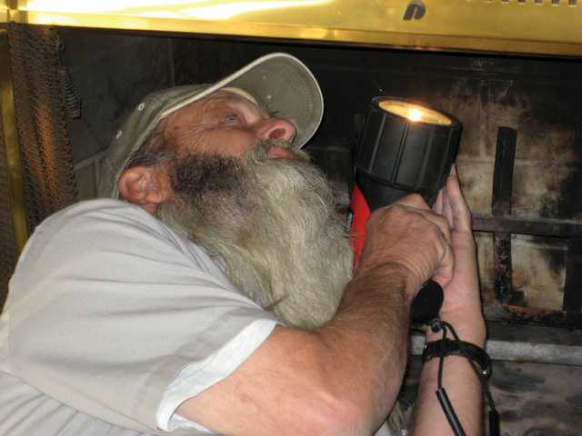 "Richard Balliger Sr. checks a fireplace's flue. The flue is the ""exhaust portal for all of the hot, poisonous gasses and soot."""