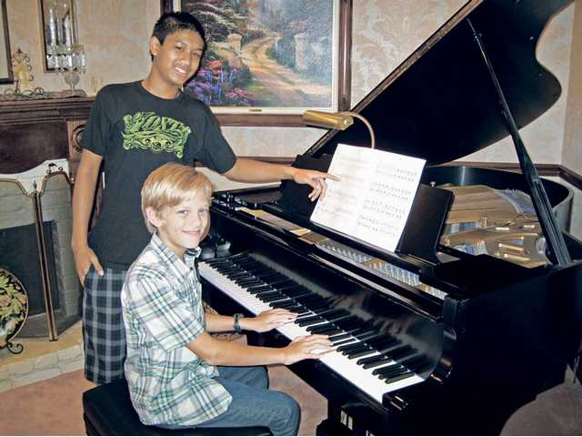 Music students Matthew Marcelino, left, and Dayton Muxlow are taught by members of the SCV Branch of the Music Teachers Association of California.