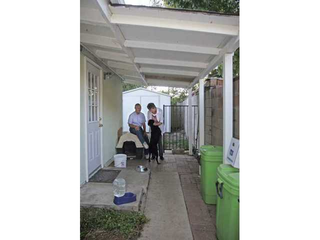 Rob and Emmy Bonja play with their dog, Penny, under an awning that must be fixed. According to the city, the awning is too close to their neighbor's property line.