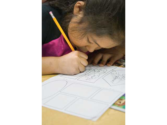 Elizabeth Nolasco, a third grader at Canyon Springs Elementary, draws in her comic book during a student art lesson program hosted by Brave New World Comics on Friday.