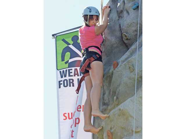 Victoria Stevens, 15, of Valencia, reaches the top of the climbing rock at the Teen Driving Safety Fair at Central Park Saturday afternoon. The event gave parents and teens information about safe driving.