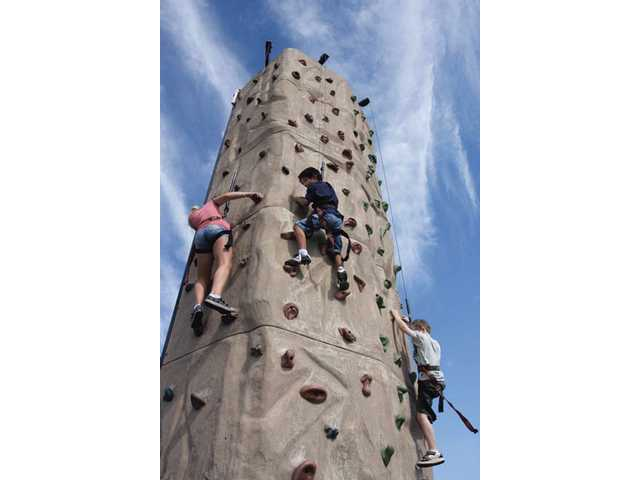 Six-year-old Todd Sadeghi of Canyon Country, center, looks down at his father as he scales the climbing wall.