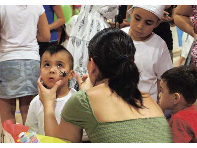 Four-year-old Romeo Garcia, of Canyon Country, has his face painted while other kids eagerly watch and wait their turn.