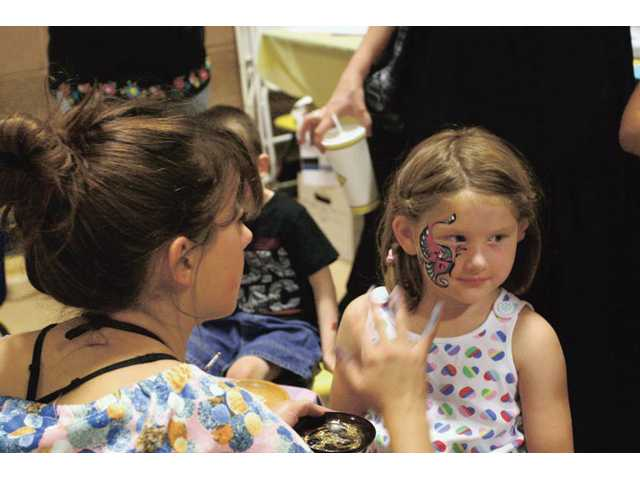 Five-year-old Kelly Smith, of Santa Clarita, has her face painted at a vendor booth at the Child & Family Center's seventh annual Kid Expo on Sunday at Golden Valley High School.