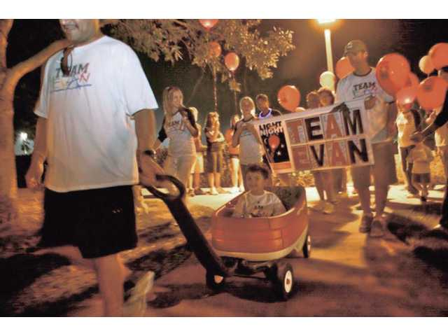 Four-year-old Evan Gabor, led by dad Bobby Gabor, smiles while 100 people participate in The Leukemia & Lymphoma Society's Light The Night Walk on Saturday. The walk raised money to help research blood cancers.