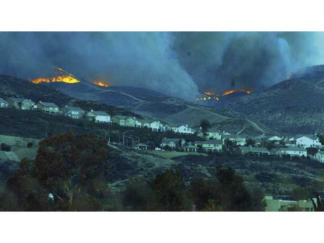 A wildfire closes on homes nestled in the foothills surrounding Santa Clarita Valley during blazes that occurred a year ago this week.