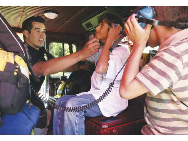 Los Angeles County firefighter Francisco Lomeli, of Station No. 132, shows 10-year-olds Nico Rotellini-Cataldi of Castaic and Zackary Kaufman of Stevenson Ranch how to properly use the head phones onboard one of the fire engines at the 'Living in the Fire Zone' event on Saturday.