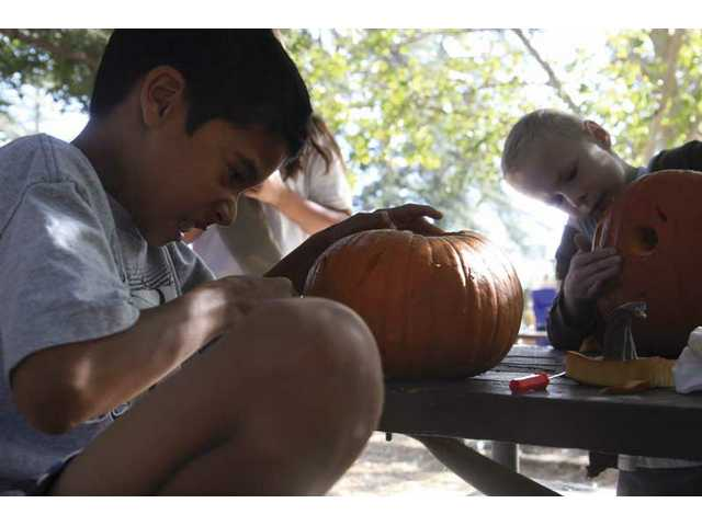 Saugus neighbors Spencer Wilson, 10, left, and John Boyer, 9, carves his pumpkin for the Heritage Haunt Pumpkin Festival on Saturday.