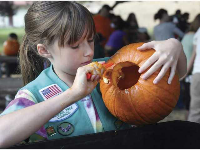 "Megan Doyel, 10, from Girl Scout troop 456, carves her pumpkin for the Heritage Haunt Pumpkin Festival contest on Saturday morning at William S. Hart Park. The event included a tour of the ""Curse of the Ghoul Mines"" maze."