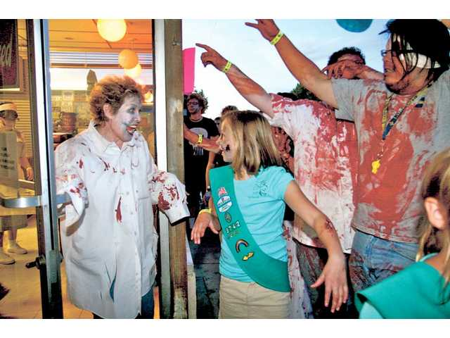 Geri Bronstrup, owner of the Way Station Coffee Shop, welcomes a group of zombies as they march down Main Street on Saturday evening. Bronstrup gave out candy brains and eyes to the zombies. More than 500 people gathered at Brave New World, in Newhall to participate in the Zombie March.